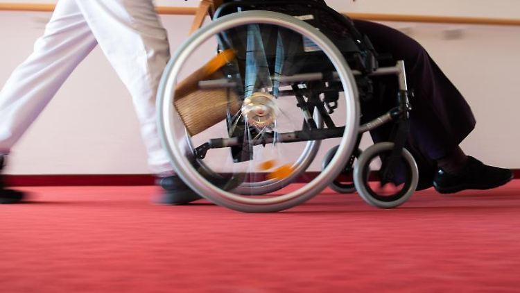 Ein Pfleger schiebt eine Pflegeheim-Bewohnerin in einem Rollstuhl. Foto: Tom Weller/dpa/Symbolbild