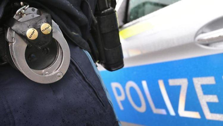 Ein Polizist mit Handschellen und einer Pistole am Gürtel steht vor einem Streifenwagen. Foto: Karl-Josef Hildenbrand/dpa/Archivbild