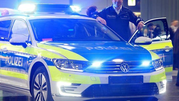 Ein Polizist steht neben einem Hybridfahrzeug, einem VW Passat GTE. Foto: Jan Woitas/dpa-Zentralbild/dpa/Archivbild