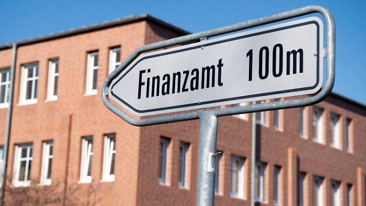 Ein Schild weist den Weg zum Eingang des Finanzamtes. Foto: Soeren Stache/dpa/Archivbild