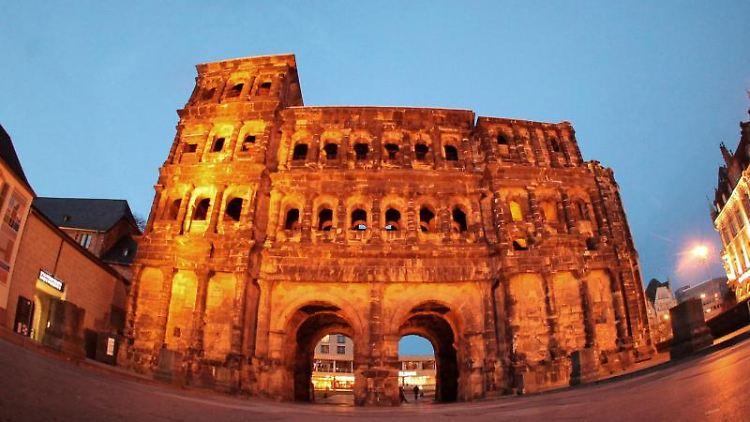 Das Wahrzeichen der Stadt Trier, die Porta Nigra, wird am Abend in der Innenstadt angestrahlt. Foto: Fredrik von Erichsen/dpa/Archivbild