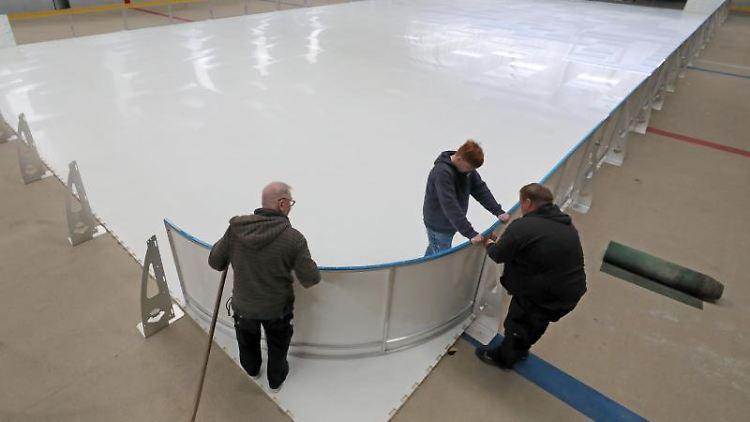 In der Eishalle motieren zwei Mitarbeiter die Kunsteis-Platten. Foto: Bernd Wüstneck/dpa-Zentralbild/dpa/Archivbild