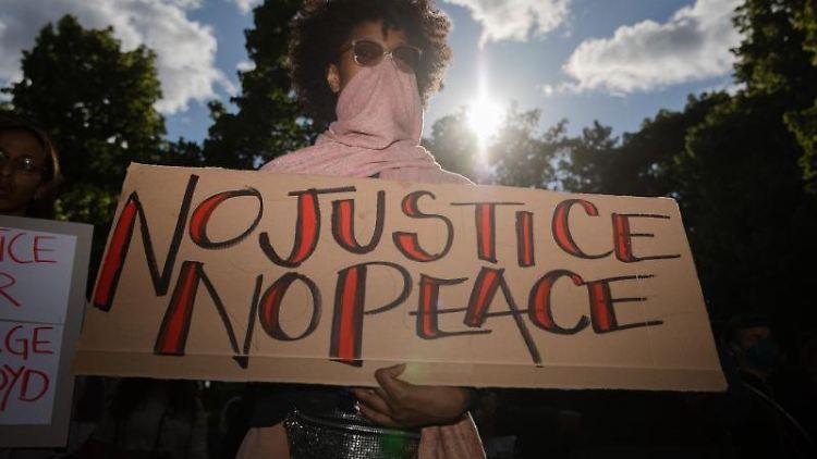 """Eine Teilnehmerin hält ein Plakat mit der Aufschrift """"No justice no peace"""". Foto: Christoph Soeder/dpa"""