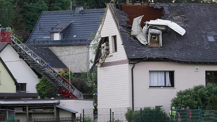 Wrackteile eines Kleinflugzeuges ragen aus dem Dach eines Wohnhauses. Foto: Thomas Frey/dpa
