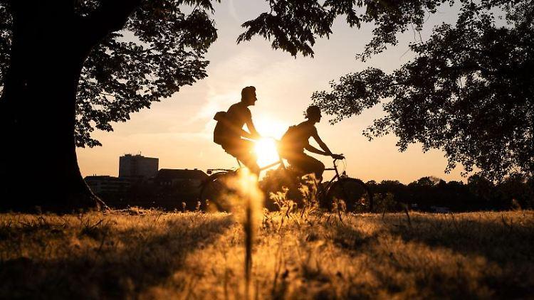 Zwei Männer fahren auf ihren Fahrrädern während im Hintergrund die Sonne untergeht. Foto: Marius Becker/dpa/Archivbild