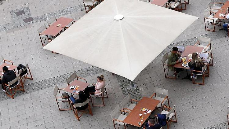 Gäste sitzen mit Abstand auf einer Außenterasse in der Innenstadt. Foto: Ronny Hartmann/dpa/Archivbild