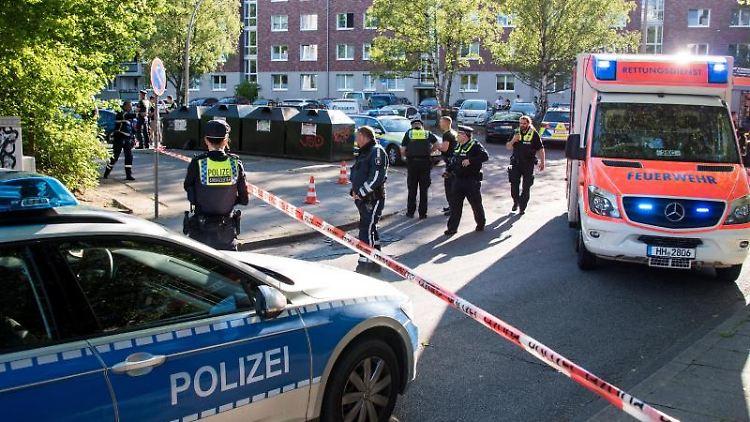 Einsatzkräfte von Polizei und Rettungsdienst stehen im Stadtteil Bergedorf an einem Tatort. Foto: Daniel Bockwoldt/dpa/Archivbild