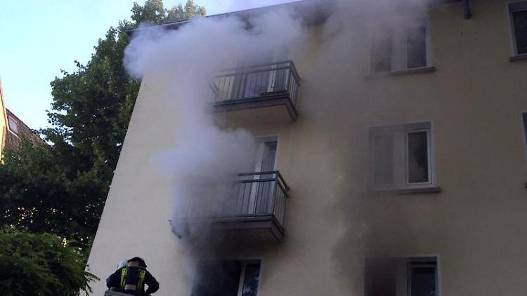 Rauch steigt über mehrere Etagen aus den Fenstern eines Hauses in Dortmund. Foto: -/Feuerwehr Dortmund/dpa