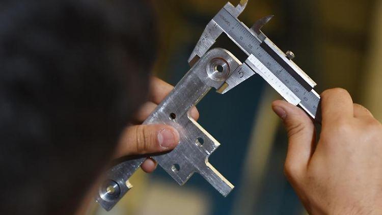 Ein Auszubildender misst ein Werkstück mit einer Schieblehre aus. Foto: Felix Kästle/dpa/Symbolbild