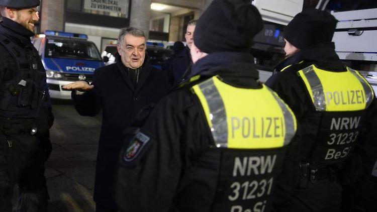 Herbert Reul (CDU, 2.v.l.) steht mit Polizisten vorm Hauptbahnhof Köln. Foto: Roberto Pfeil/dpa/Archivbild