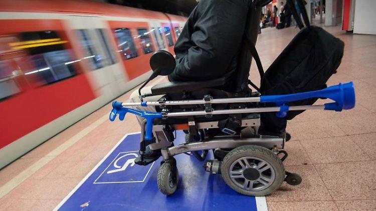 Ein Mann sitzt mit seinem Elektro-Rollstuhl an einem Bahnhof am Gleis. Foto: Marijan Murat/dpa/Symbolbild