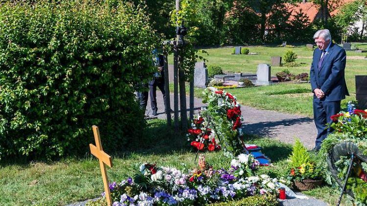 Der Hessische Ministerpräsident Volker Bouffier (CDU)gedenkt dem ermordeten Politiker Lübcke an dessem Grab. Foto: Staatskanzlei/T. Lohnes/dpa