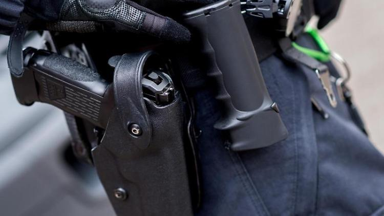 Ein Beamter trägt die Dienstwaffe am Gürtel. Foto: Hauke-Christian Dittrich/dpa/Archivbild