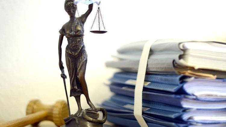 Eine modellhafte Nachbildung der Justitia neben Aktenordnern. Foto: Volker Hartmann/dpa/Symbolbild