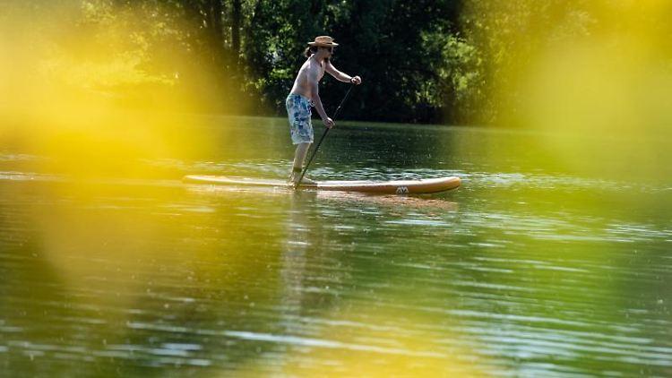 Mit einem Stand-up-Paddle-Board ist Dennis aus Göttingen auf dem Wendebach-Stausee unterwegs. Foto: Swen Pförtner/dpa