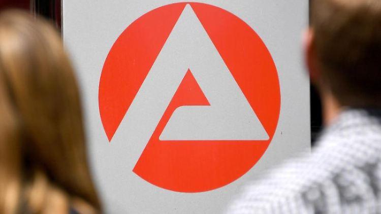 Zwei Personen stehen vor dem Logo der Agentur für Arbeit. Foto: Carsten Rehder/dpa/Archivbild