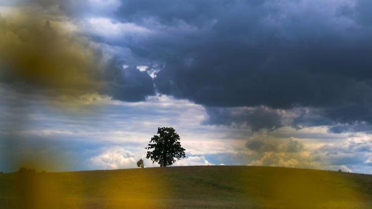 Regenwolken ziehen über die Landschhaft bei Höhenrain im Landkreis Starnberg. Foto: Stephan Jansen/dpa/Archivbild