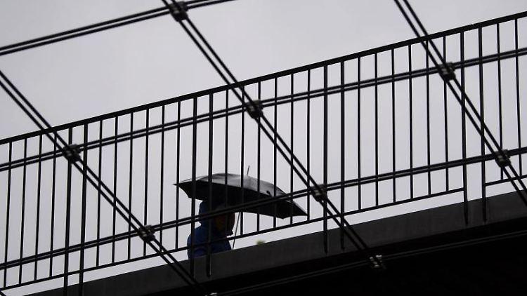 Eine Frau geht mit ihrem Regenschirm über eine Brücke. Foto: Marijan Murat/dpa/Archivbild