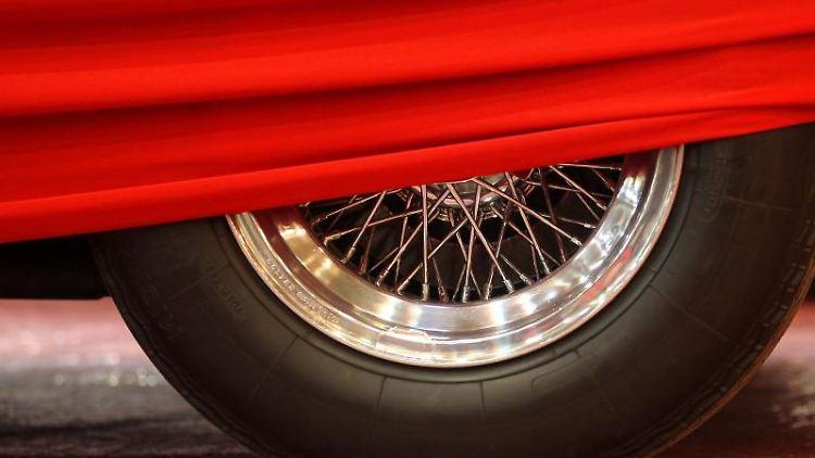 Der Reifen eines Autos schaut unter einer roten Abdeckung hervor. Foto: picture alliance / dpa / Symbolbild
