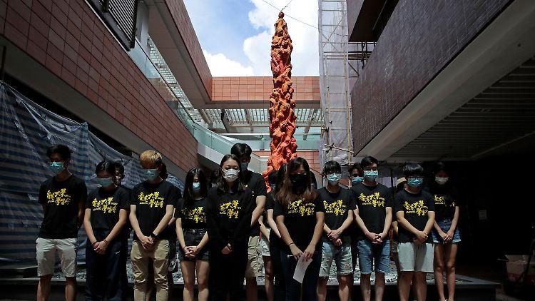 Studierende halten vor der Statue der