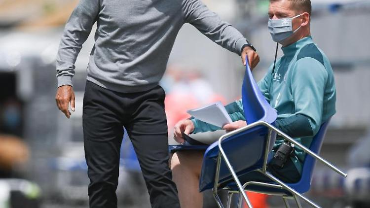 Paulis Trainer Jos Luhukay (l.) nimmt sich vor dem Spiel einen Stuhl. Foto: Matthias Hangst/Getty Images Europe/Pool/dpa