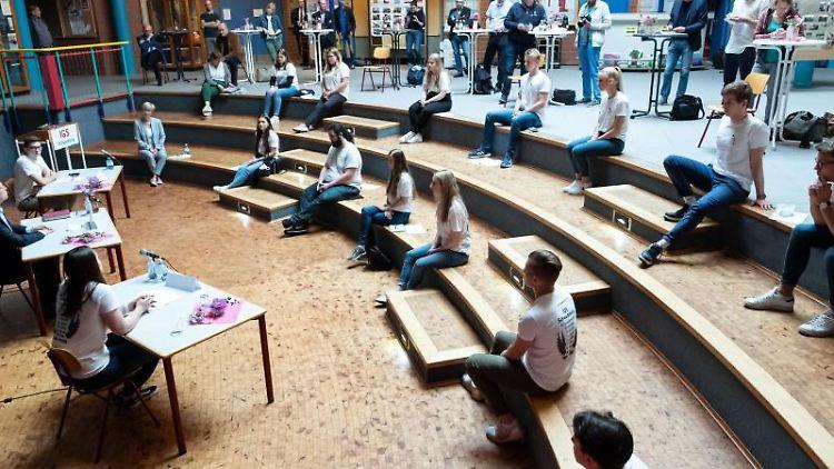 Stephan Weil (SPD, l.) und Schüler und Schülerinnen. Foto: Peter Steffen/dpa