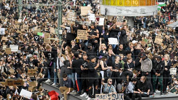 Teilnehmer einer Kundgebung auf dem Alexanderplatz protestieren gegen Rassismus und Polizeigewalt. Foto: Britta Pedersen/dpa-Zentralbild/dpa