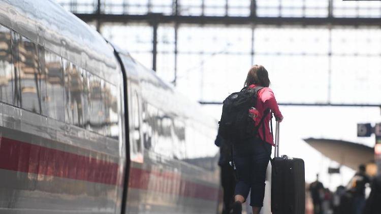 Eine Reisende geht am Gleis des Frankfurter Hauptbahnhofs mit ihrem Koffer zu einem wartenden ICE. Foto: Arne Dedert/dpa