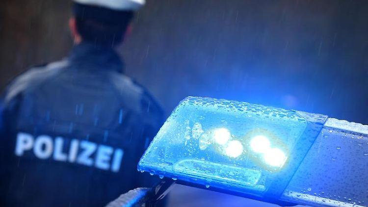 Ein Polizist steht im Regen vor einem Streifenwagen dessen Blaulicht aktiviert ist. Foto: Karl-Josef Hildenbrand/dpa/Illustration
