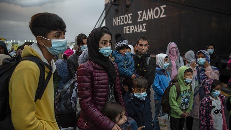 Migrantinnen und Migranten aus dem Lager Moria, die mit einem Schiff von der Insel Lesbos gekommen sind, stehen nach ihrer Ankunft im Hafen von Piräus bei Athen.