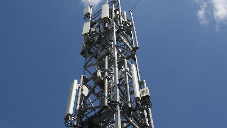 Das Foto zeigt einen Mobilfunkmast mit 5G-Antennen. Foto: Christoph Dernbach/dpa/Archivbild