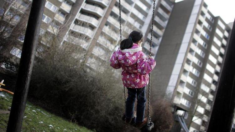 Ein Kind schaukelt vor einem Hochhaus in Meschenich bei Köln. Foto: picture alliance / dpa / Archiv / Symbolbild