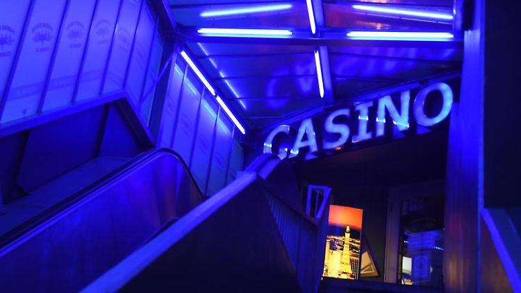 Der Eingang eines Casinos strahlt in blauem Neonlicht. Foto: Sonja Wurtscheid/dpa/Symbolbild