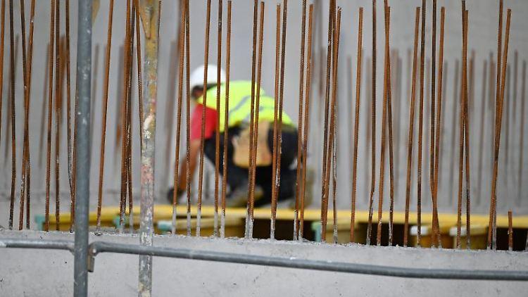 Ein Handwerker arbeitet auf einer Baustelle an Betonstahlträgern. Foto: Patrick Seeger/dpa/Symbolbild
