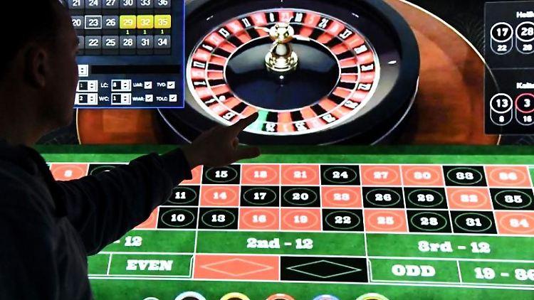 Ein Mann steht vor einem Bildschirm mit einer Seite für Online-Roulette. Foto: Carsten Rehder/dpa/Symbolbild