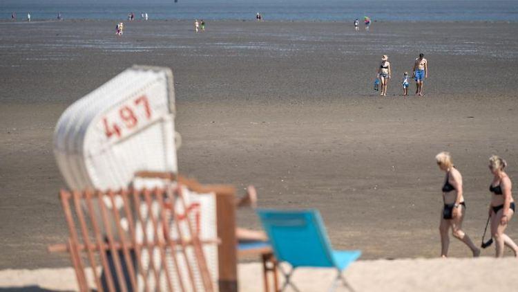 Urlauber spazieren bei Niedrigwasser am Strand entlang. Foto: Sina Schuldt/dpa/Archivbild