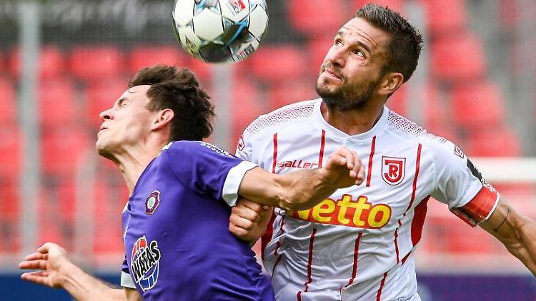 Clemens Fandrich von Erzgebirge und Marco Grüttner von Regensburg (l-r.) im Zweikampf um den Ball. Foto: Armin Weigel/dpa