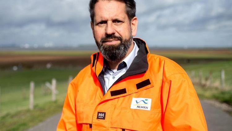 Olaf Lies (SPD), Umweltminister in Niedersachsen, steht auf dem Deich derEms. Foto: Hauke-Christian Dittrich/dpa/Archivbild