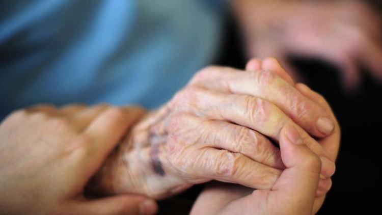 Eine Pflegekraft hält in einem Seniorenheim die Hand einer Bewohnerin. Foto: Daniel Reinhardt/dpa/Symbolbild
