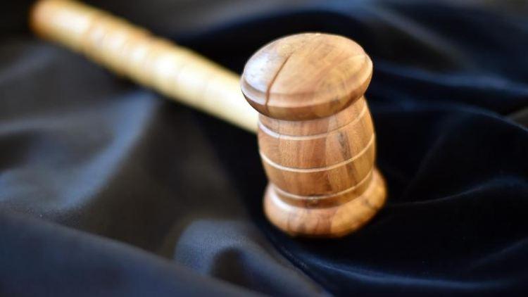 Auf einem Tisch in einemGericht liegt ein Richterhammer aus Holz, darunter eine Richterrobe. Foto: picture alliance / dpa/Symbolbild