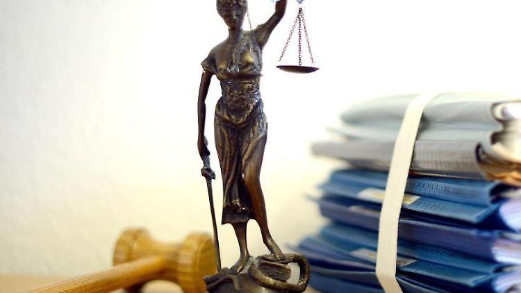 Die modellhafte Nachbildung der Justitia steht neben einem Holzhammer und einem Aktenstapel. Foto: Volker Hartmann/dpa