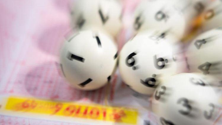 Lotto-Kugeln liegen auf einem Lottoschein. Foto: Tom Weller/dpa/Archivbild