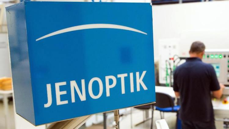 Ein Mitarbeiter steht neben einem Schild der Jenoptik AG. Foto: Sebastian Kahnert/ZB/dpa/Symbolbild