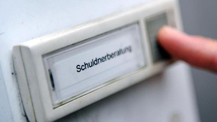 Ein Mann klingelt bei der Schuldnerberatung. Foto: Angelika Warmuth/dpa/Symbolbild