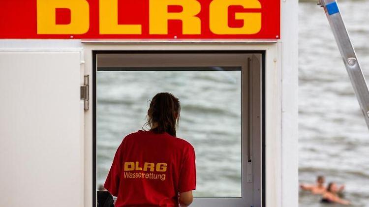 Eine Rettungsschwimmerin der DLRG steht vor dem Fenster eines Wachturms. Foto: Mohssen Assanimoghaddam/dpa/Symbolbild