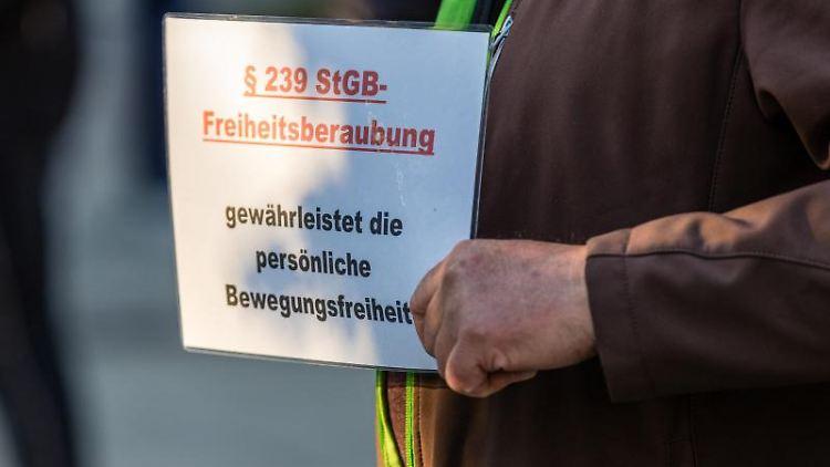 Ein Teilnehmer einer Demonstration hält ein Plakat. Foto: Frank Hammerschmidt/dpa-Zentralbild/dpa/Symbolbild