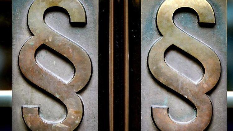 Paragrafen-Symbole sind an Türgriffen am Eingang zu einem Gericht. Foto: Oliver Berg/dpa/Illustration