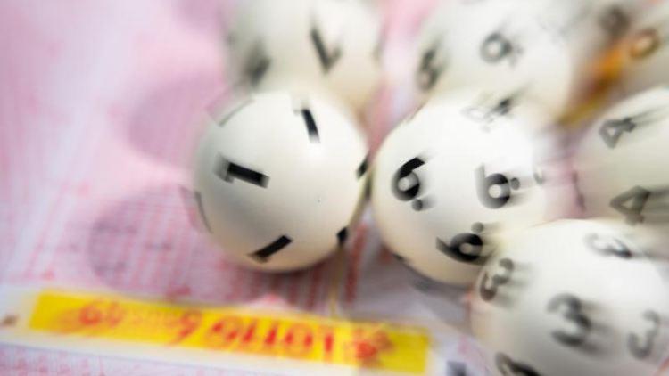 Lotto-Kugeln liegen auf einem Lottoschein. Foto: Tom Weller/dpa/Archiv/Symbolbild