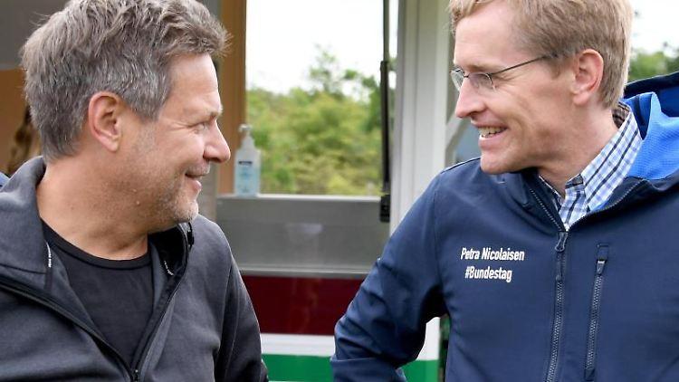 Daniel Günther (CDU,r) und Robert Habeck (Bündnis90/Die Grünen) unterhalten sich. Foto: Carsten Rehder/dpa/Archivbild