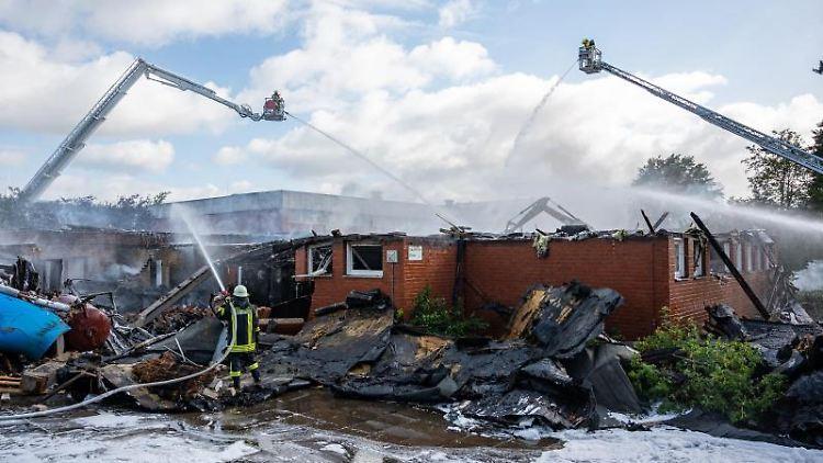 Feuerwehrleute löschen den Brand einer Schule. Foto: Daniel Reinhardt/dpa